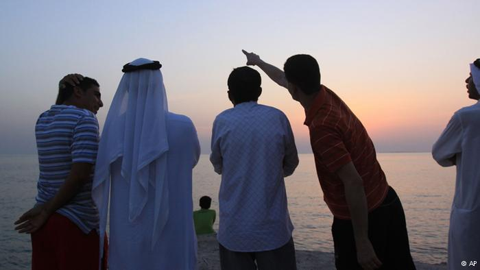 Men at the seaside in Bahrain at sunset. Photo: AP