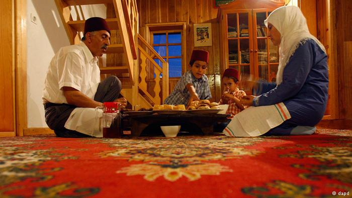 A Bosnian Muslim family sitting on the floor of their home for the Iftar meal. Photo: dapd