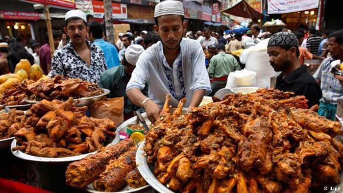Stallholders and plates loaded with cooked meat at a market in Dhaka. Photo: dapd