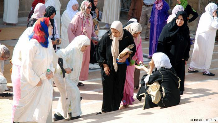 Four women giving alms to another woman sitting on the street in Morocco. Photo: DW/M. Houbice