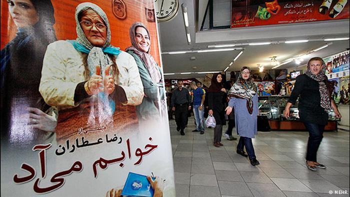People shopping in a mall in Iran in the evening, a film poster in the foreground. Photo: MEHR