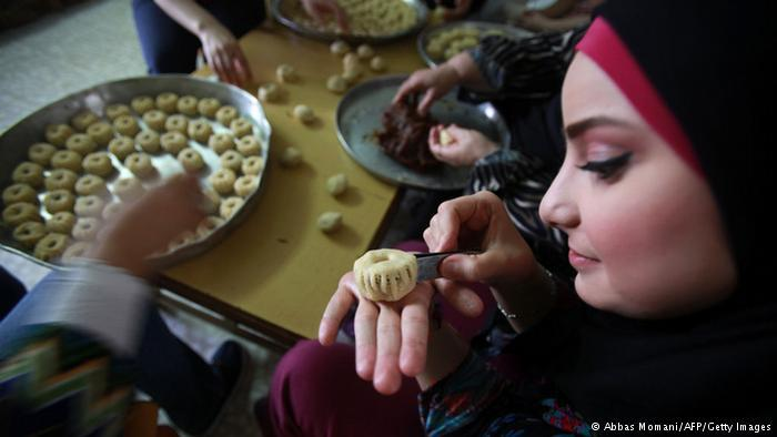 Woman in Ramallah in front of plates of sweetmeats. Photo: Abbas Momani/AFP/Getty Images