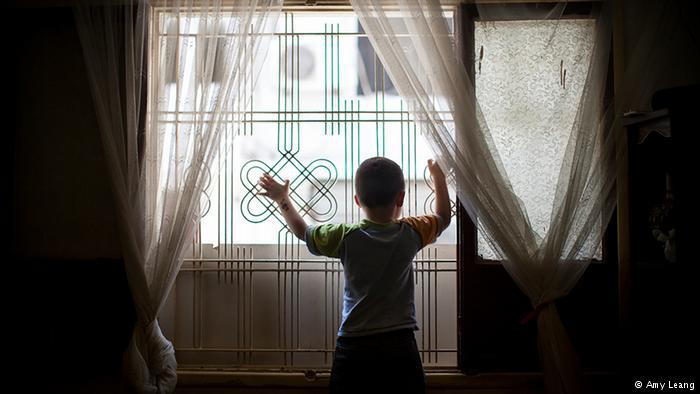 A Syrian-Armenian child refugee standing at a window in Beirut (photo: Amy Leang)