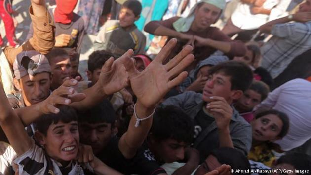 Desperate refugees reaching up for water (photo: Ahmad Al-Rubaye/AFP/Getty Images)