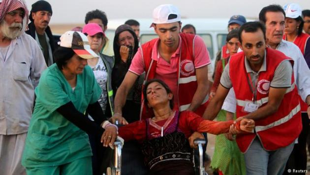 Members of the Red Crescent help a Yazidi woman (photo: Reuters)