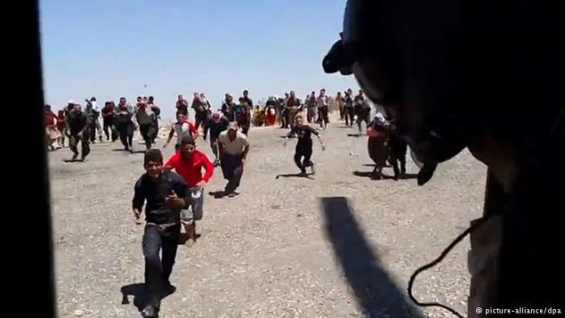 Refugees run towards a helicopter (photo: picture-alliance/dpa)