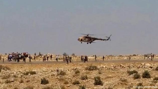 Refugees run towards an approaching Iraqi helicopter (photo: picture-alliance/dpa)