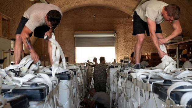 US Army soldier parachute riggers prepare pallets of water for a humanitarian air drop, 6 August 2014 (photo: picture-alliance/dpa)