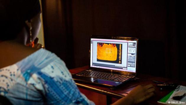 A woman looks at an image of a manuscript on a laptop screen (photo: DW/P. Breu)