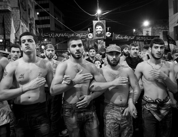 Young Shia men pounding their chests beneath a poster of Hezbollah's leader, Hassan Nasrallah, Nabatiyeh, Lebanon, November 2014 (photo: Maya Hautefeuille)