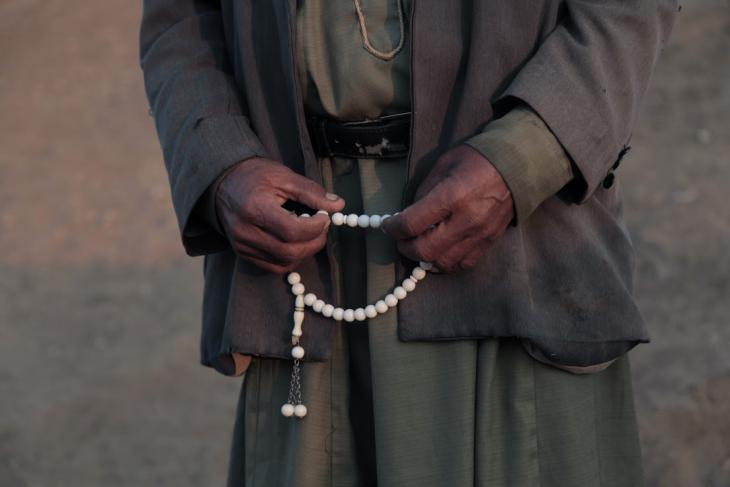 Ehmaid Kaabneh holds his prayer beads as he tends his sheep, Al-Maleh, West Bank, October 2014 (photo: Mohammad Alhaj)