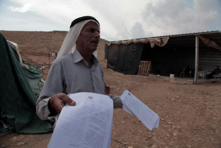 Mahmoud Awwad Ayoub holding notification from the IDF ordering him to leave, Al-Maleh, West Bank, October 2014 (photo: Mohammad Alhaj)