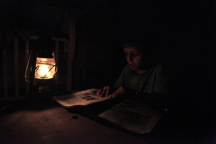A Bedouin boy does his homework by lamp light, near Tubas, West Bank, October 2014 (photo: Mohammad Alhaj)