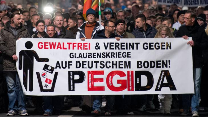 "People marching behind a banner reading ""non violent and united against religious wars on German soil! PEGIDA"" (photo: picture-alliance/dpa/Arno Burgi)"