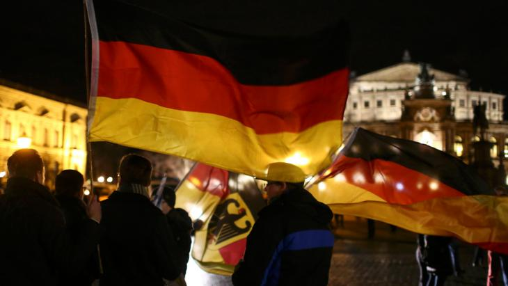Pegida supporters waving German flags at a march in Dresden (photo: Reuters/Hannibal Hanschke)