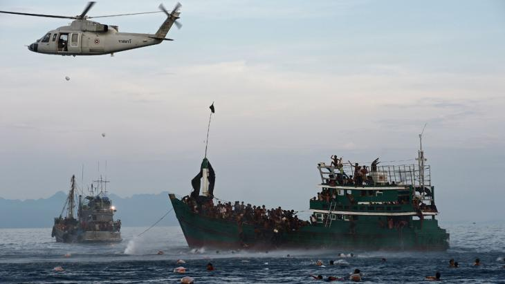 Rohingya migrants swim to collect food supplies dropped by a Thai army helicopter (photo: Getty Images/Afp/C. Archambault)