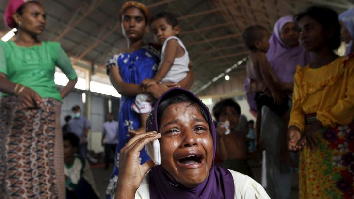 Migrant crying on a mobile phone, Kuala Langsa, Indonesia (photo: Reuters/R. Bintang)