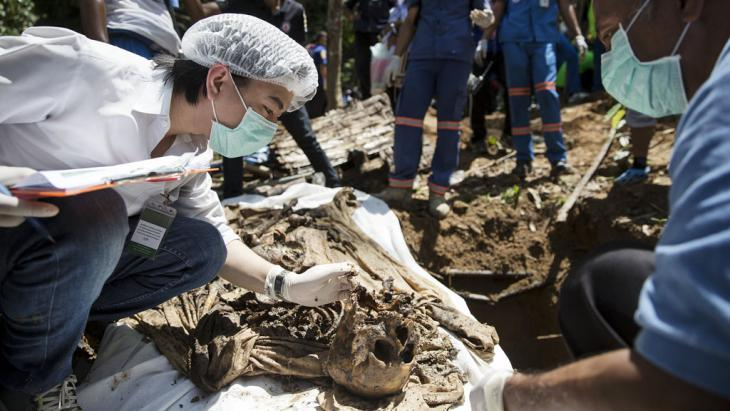A forensic expert inspects human remains found in a mass grave in Thailand (photo: Reuters/D. Sagolj)
