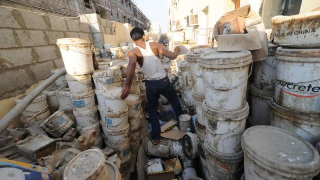 A foreign worker surrounded by empty paint pots (photo: picture-alliance/dpa)
