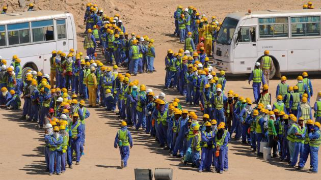 Foreign workers queuing for buses (photo: picture-alliance/dpa)