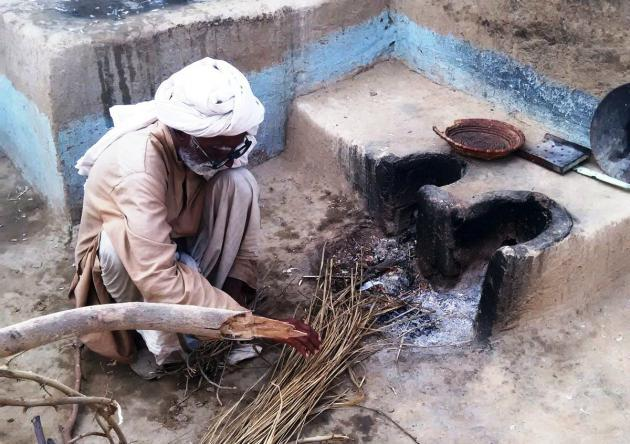 An elderly man prepares to light a fire in an outdoor hearth (photo: Usman Mahar)