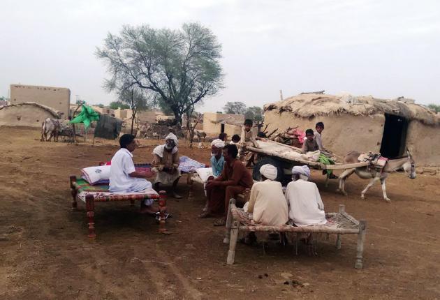 Men sitting on charpoys outside their homes, Cholistan desert, Pakistan (photo: Usman Mahar)