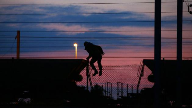 A refugee climbs over a fence near the entrance to the Channel Tunnel (photo: picture-alliance/empics/Y. Mok)