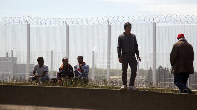 Refugees near a security fence in Calais (photo: DW/L. Scholtyssek)