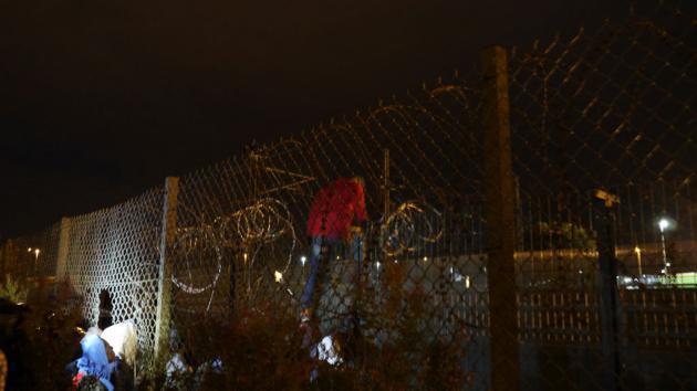 A refugee climbs over a Eurotunnel security fence in Calais (photo: DW/B. Riegert)