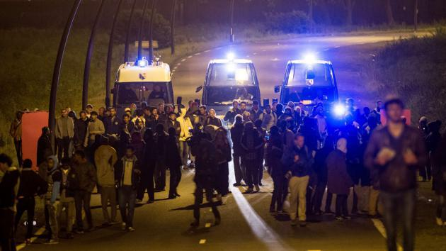 Police vehicles escorting migrants away from the entrance to the Channel Tunnel (photo: Getty Images/AFP/P. Huguen)