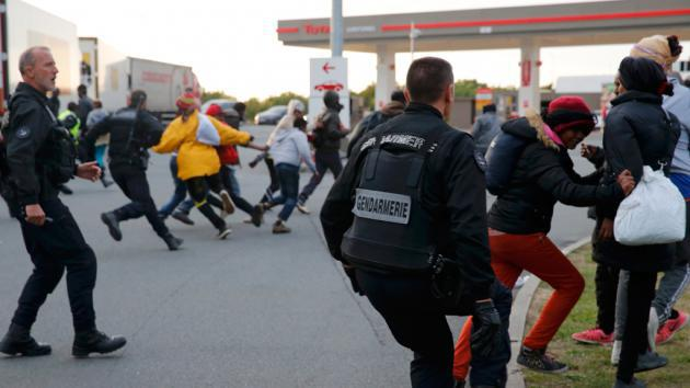 French police officers chase migrants away from a closed petrol station, which was used as a meeting point for those wishing to cross the Channel Tunnel to England (photo: Reuters/P. Rossignol)