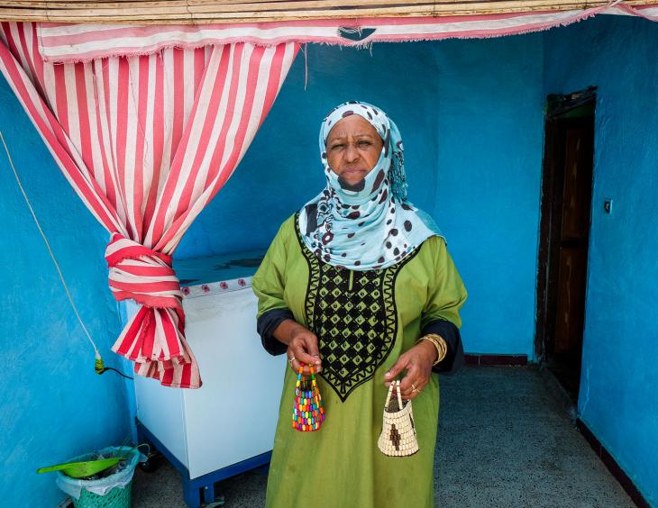 A woman on Suheil Island with baskets she has made to sell to tourists (photo: Maya Hautefeuille)