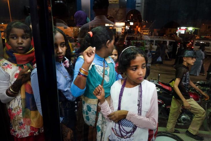 Teenage girls peer into a photography studio in Aswan (photo: Maya Hautefeuille)