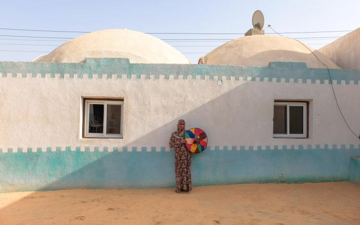 A West Aswan woman holding a ″tegiddy″ stands in front of her new extension (photo: Maya Hautefeuille)