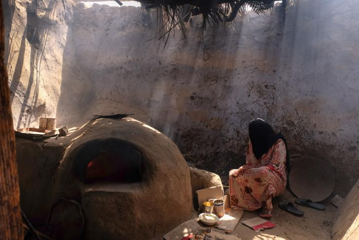 A woman on Suheil Island bakes loaves of bread in her communal outdoor kitchen (photo: Maya Hautefeuille)