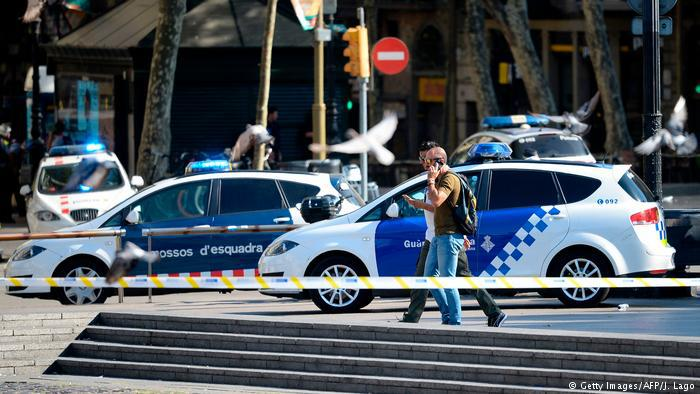 Police phone as they walk past police cars