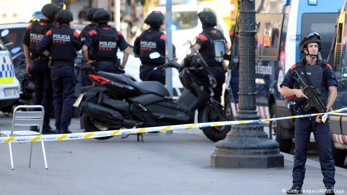 Armed policemen stand in a cordoned-off area