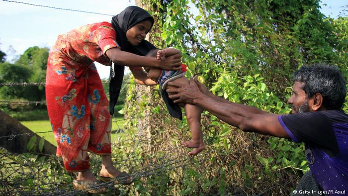 A Rohingya man passes an infant through a barbed wire border fence