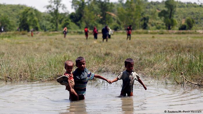 Rohingya children wade through water