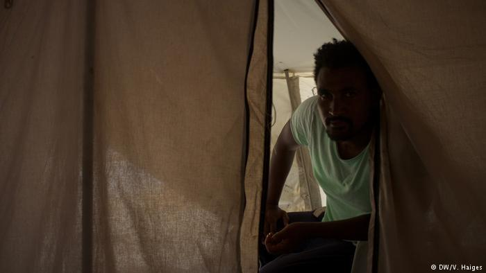 An Ethiopian asylum-seeker peers out of a tent on Lesbos