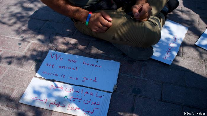 A man sits behind protest signs placed on the ground