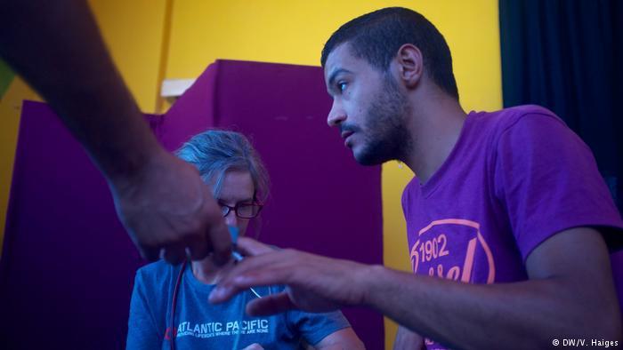A doctor checks a man's pulse during a health clinic