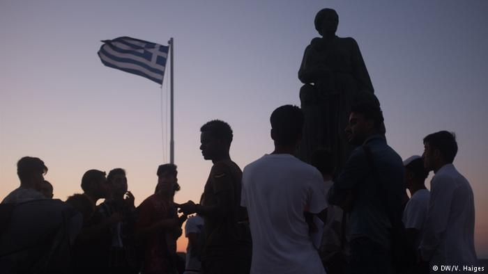 Asylum-seekers stand in front of a statue and a Greek flag on Lesbos
