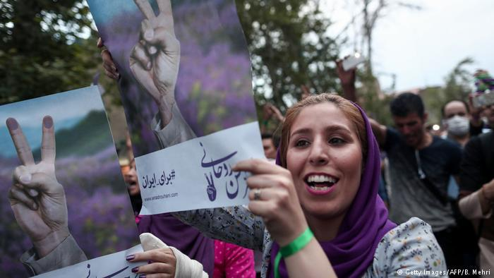 Supporters of newly re-elected Iranian President Hassan Rouhani hold placards as they celebrate his victory in Tehran