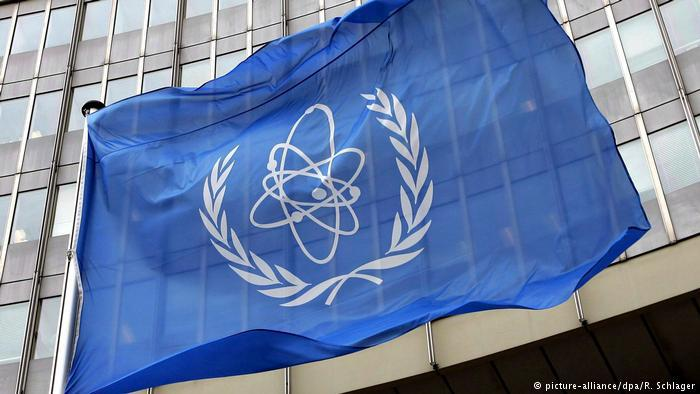 A flag bearing the symbol of the International Atomic Energy Agency (IAEA) waves outside the UN building in Vienna