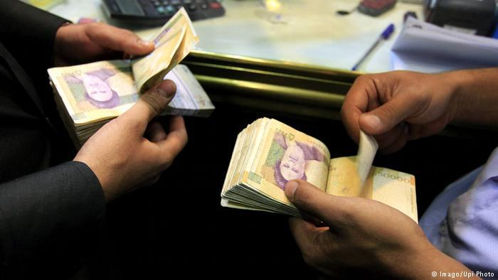 Iranian men count their 50,000 rial banknotes
