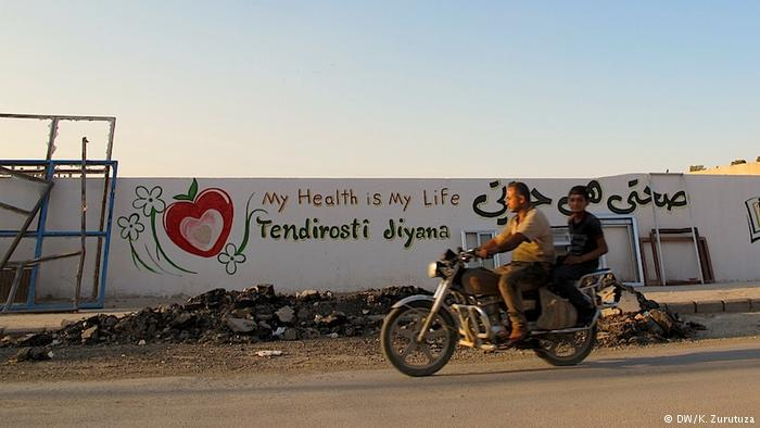 A man and a boy on a motorcycle ride past a mural in Kobani (photo: DW/Zurutuza)