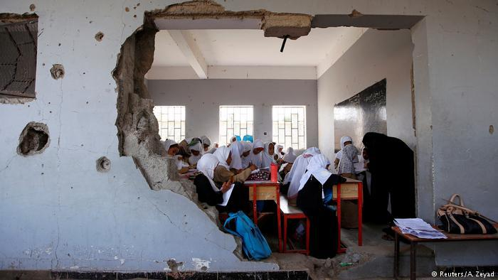 Girls with white headscarves in a ruined Yemeni classroom (photo: Reuters/A. Zeyad)