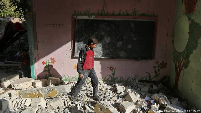 Boy walking on rubble in the town of Hamouria, near Damascus, Syria (photo: Getty Images/AFP/A. Almohibany)