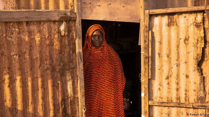 A woman stands in a doorway to a makeshift shack